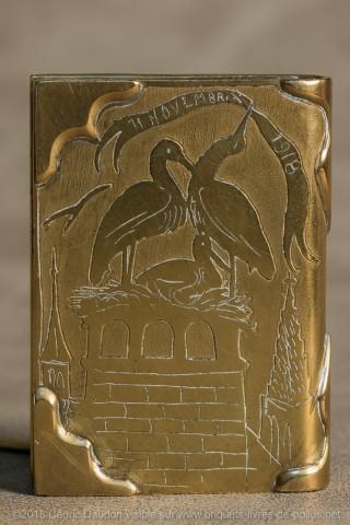 Face 1 : Briquet fêtant l'armistice selon la banderole au bec de la cigogne. Avec le couple il y a un cigogneau dans le nid sur une cheminée typique. En arrière-plan deux clochers faisant sans doute référence à la cathédrale de Strasbourg.  Face2 : Porte