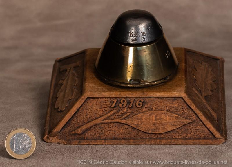 Encrier avec tête d'obus insérée dans une base en bois sculptée de motifs floraux et daté « 1916 ».