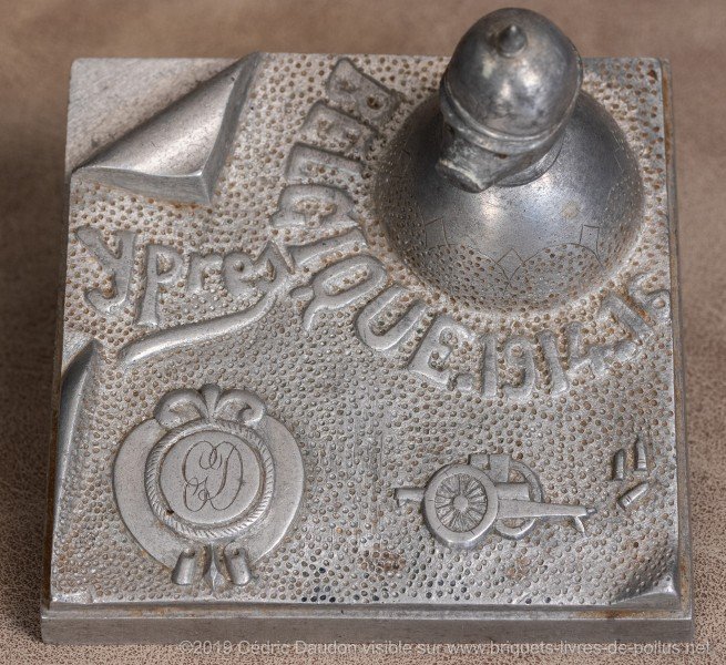Encrier en aluminium fondu gravé « Belgique 1914 1915 Ypres ». Bouchon de réservoir en forme de tête de cochon coiffée d'un casque à pointe. Signé sous la terrasse « Duclos août 1916 ». Je crois qu'il y a d'autres modèles identiques, ce qui laisse suppose