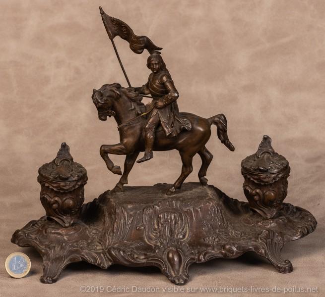 Grand encrier avec la représentation basique de Jeanne d'Arc sur son destrier tenant un oriflamme aux armes du royaume de France et la mention Jésus Maria.