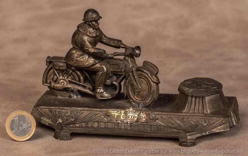 Signé Ouvet et marqué « Souvenir de Coetquidan ». Qui reconnaîtra la marque de la moto et son millésime ?