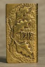 2 briquets ayant le même concepteur, structure identique et motifs estampés à feuilles de chêne comparables.